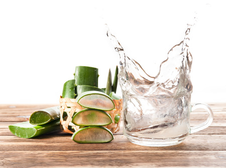 木製の背景でアロエベラ健康ドリンクのスプラッシュ 写真素材