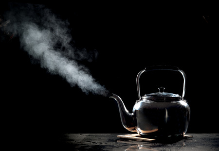 Tea kettle with boiling water on a black background