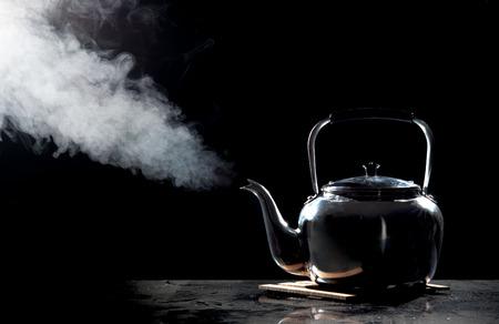 Ketel van de thee met kokend water op een zwarte achtergrond