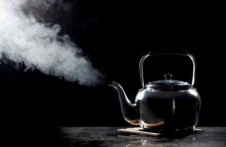 black water: Tea kettle with boiling water on a black background