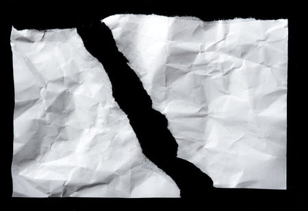 White torn of paper isolated on a black background. Foto de archivo