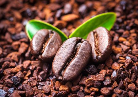 Grano de café sobre fondo café molido.