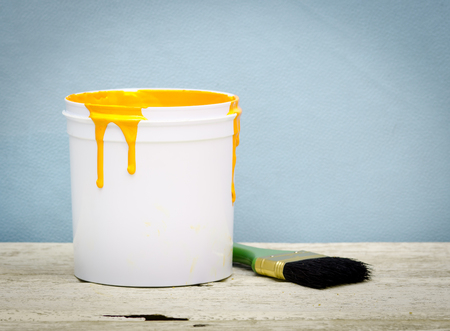 yellow paint: White plastic bucket with yellow color paint and brush on wood,vintage background