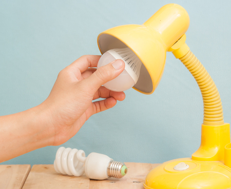 electricity background: Hand changing a regular light bulb for LED,vintage background Stock Photo