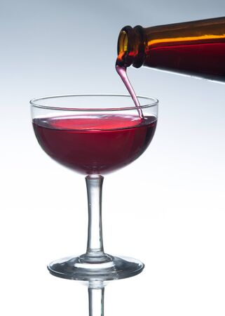 red wine pouring: Red wine pouring into wine glass
