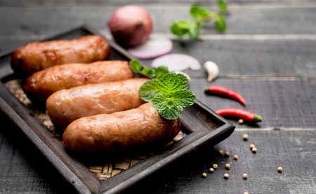 free dish: Fried sausages with herbs on black wood