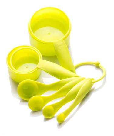 at close quarters: Green assortment measuring cups and spoons for baking or cooking on a white background