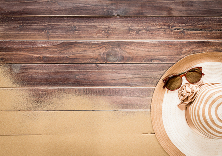 Sea sand with Straw hat,sunglasses on wooden floor,Top view with copy space