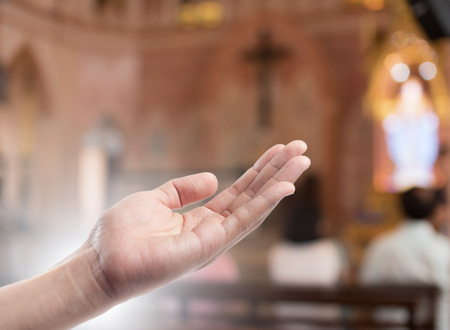 forgiven: Human open empty hand with palms up(Praying Hand) on blurred church interior background Stock Photo