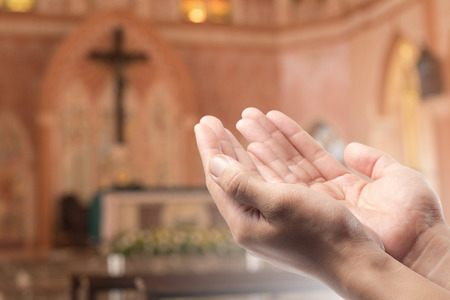 Human open empty hand with palms up(Praying Hand) on blurred church interior background Stockfoto