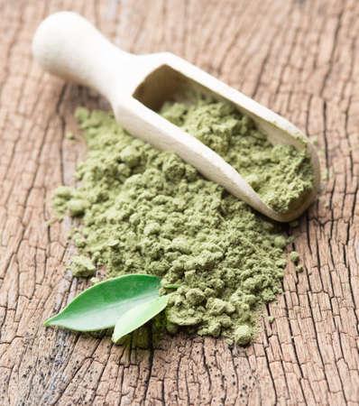 maccha: powder green tea with green tea leaf and scoop on wood background