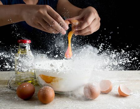 Hands breaking an egg with Flying flour on table wood