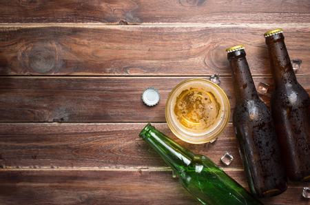 ボトル キャップと素朴な木材の背景、テキスト、平面図用のスペースのびんビール グラス