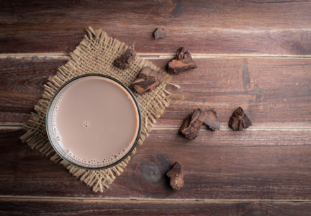 Glass of chocolate milk on wood table,top view