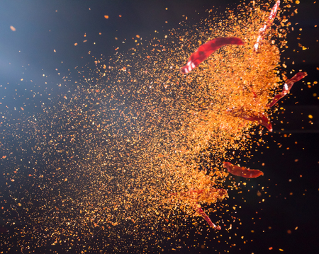 Cayenne pepper powder explosion isolated on black background,Flying Cayenne pepper,Motion blur Stock Photo