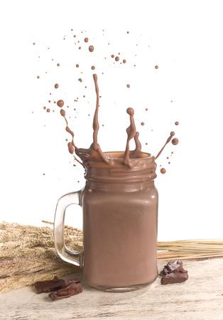 Melkchocolaplons op houten lijst over witte achtergrond Stockfoto