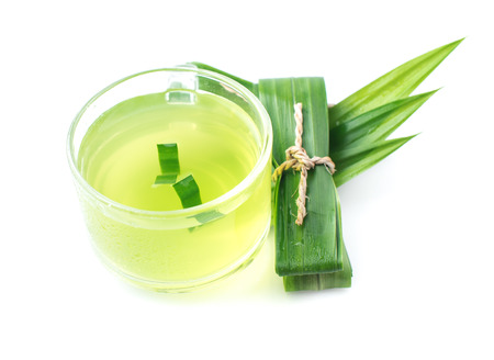 Glass of pandan juice and pandan leaves on white background