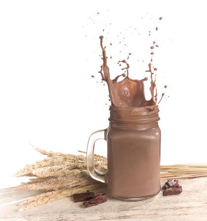 Milk chocolate splash on wood table over white background