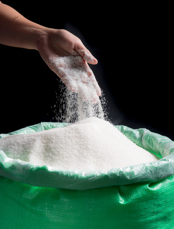 Sugar being poured from hand into bag of sugar on dark background