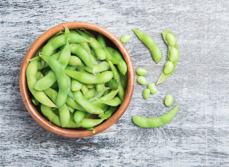 Green Japanese Soybean in wooden bowl on table wood,top view Archivio Fotografico