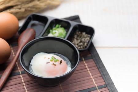 Soft boiled egg or onsen egg on wooden