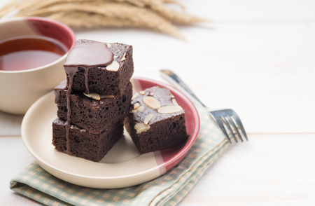 Chocolate Brownie with chocolate topping on white wood