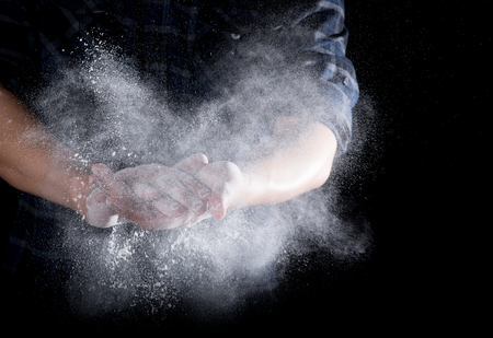 Chef hand clap with splash of white flour and black background Stock Photo