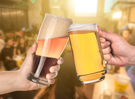 leisure and drinks concept , male hands clinking beer mugs at bar or pub