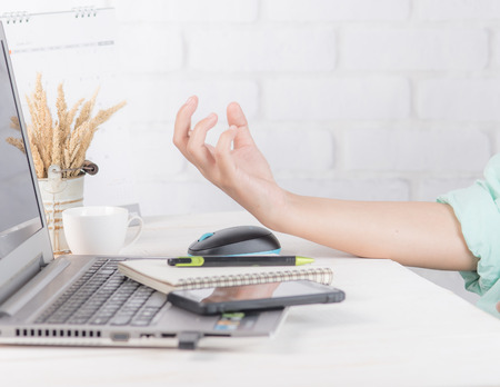 Hand pain caused at office desk in front of laptop,Office syndrome Stock Photo