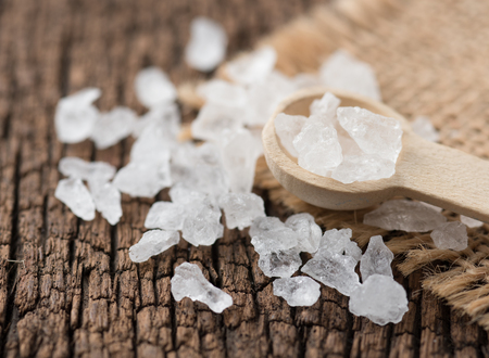 Rock sugar with spoon on wood background.