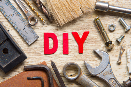 DIY,DO IT YOURSELF word made from wooden letters with set of tools on wood background Stockfoto
