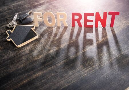 Symbol of the house with text FOR RENT and key on wooden background