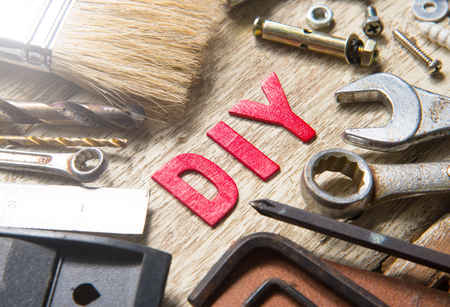 DIY,DO IT YOURSELF word made from wooden letters with set of tools on wood background Imagens