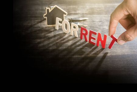 Symbol of the house with text FOR RENT and key on wooden background,humans finger