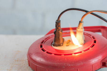 Electricity short circuit,Fire in overloaded power strip. Stock Photo