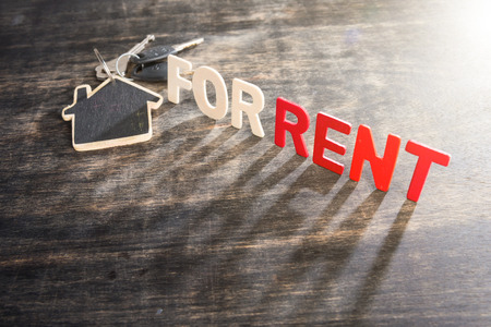"Symbol of the house with text ""FOR RENT"" and key on wooden background"