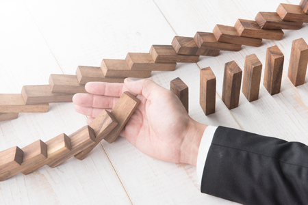 Businessman hand trying to stop toppling dominoes on wood,stop domino effect 免版税图像
