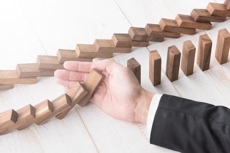 Zakenman hand probeert om te stoppen met domino's op hout te stoppen, domino effect te stoppen Stockfoto