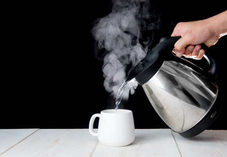 kettle pouring boiling water into a cup with smoke on wood table Stok Fotoğraf - 83293505