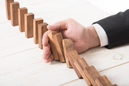 Businessman hand trying to stop toppling dominoes on wood,stop domino effect Stock Photo
