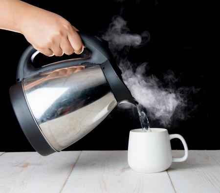 木製テーブルの上の煙をカップに沸騰したお湯を注ぐポット 写真素材