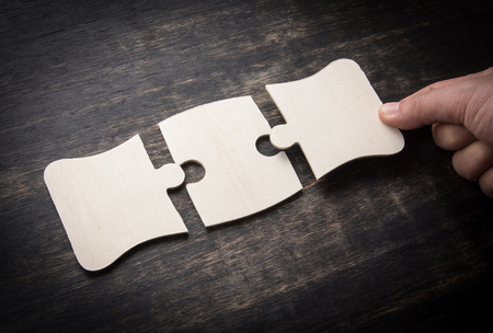 Hand holding jigsaw puzzles on a rustic wooden,wooden puzzle.