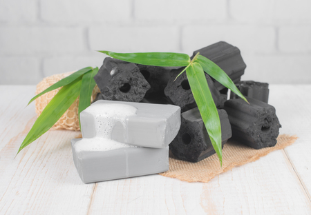 Black coal bar of soap with wood charcoal on dark wood,top view Stock Photo