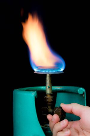 Male hand turning gas stove on a black background, operating valve of gas cylinder