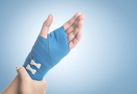 Hand wrapped in elastic bandage on blue background,hand pain