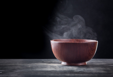 Steam of hot soup in a soup bowl with smoke on black background