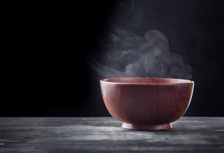 Vapor de sopa caliente en un plato de sopa con humo sobre fondo negro Foto de archivo