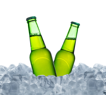 Cold bottle of beer with drops in ice cubes isolated on a white Stock Photo