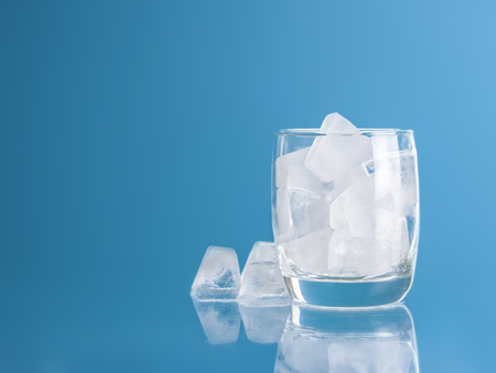 Empty glass with ice cube on blue background