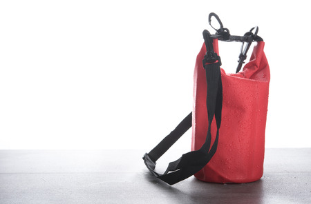 Red waterproof bag for protect your belonging from water on wood table Stock Photo
